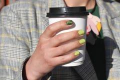 A mão fêmea bonita com tratamento de mãos guarda o copo de café do cartão O verniz para as unhas amarelo macio e o olho de gato v Fotografia de Stock Royalty Free