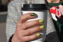 A mão fêmea bonita com tratamento de mãos guarda o copo de café do cartão O verniz para as unhas amarelo macio e o olho de gato v Foto de Stock Royalty Free