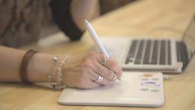 A mão fêmea com anéis tira usando uma tabuleta de gráficos que senta-se na tabela filme