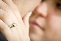 Mão fêmea com a cara de Ring Touching Fiance do acoplamento imagem de stock royalty free