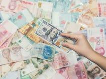 Mão fêmea com dinheiro de 3Sudeste Asiático e de nota de dólar do americano cem A moeda de Hong Kong, Indonésia, Malásia, tailand Fotos de Stock