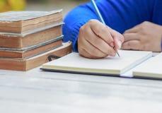 Mão fêmea com escrita da camisa da mola algo com lápis Imagem de Stock