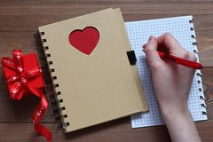 A mão fêmea com o punho faz notas na folha de papel de um caderno com coração vermelho em uma tabela de madeira Foto de Stock