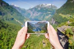 Mão fêmea com o telefone que fotografa o fiorde de Geiranger, Noruega Fotografia de Stock Royalty Free