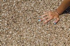 Mão fêmea com os pregos cianos que afundam-se na areia Fotografia de Stock Royalty Free