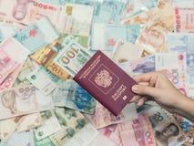 Mão fêmea com passaporte e dinheiro de 3Sudeste Asiático e de nota de dólar do americano cem currency Fotografia de Stock Royalty Free