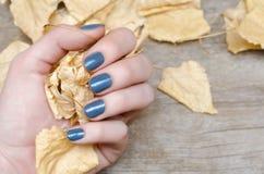Mão fêmea com projeto azul do prego Fotografia de Stock Royalty Free