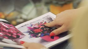 Mão fêmea com um fim vermelho do tratamento de mãos acima Dedos fêmeas que deslizam através da brochura floristic filme
