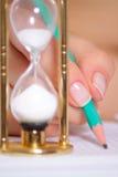 A mão fêmea com um lápis e uma areia cronometram Imagem de Stock Royalty Free