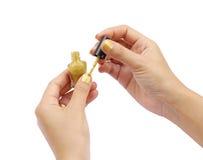 Mão fêmea com um verniz para as unhas dourado Imagem de Stock