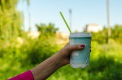 Mão fêmea com um vidro de papel Fotografia de Stock Royalty Free