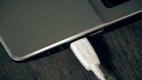 A mão fêmea conecta dois fios dos cabos de USB ao laptop closeup video estoque