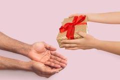 A mão fêmea dá o presente ao noivo imagens de stock royalty free