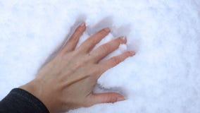 A mão fêmea deixa uma impressão em um monte de neve da neve video estoque