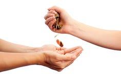 A mão fêmea derrama abaixo das moedas nas mãos de outras Foto de Stock Royalty Free