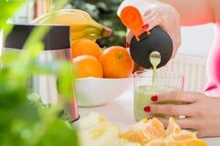 A mão fêmea derrama o cocktail feito do fruto fresco foto de stock royalty free