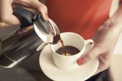 A mão fêmea derrama uma bebida no copo do fabricante de café imagem de stock royalty free