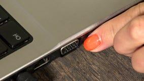 A mão fêmea desconecta o fio preto do cabo de USB do laptop closeup video estoque