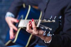 Mão fêmea do close-up que joga na guitarra acústica Foto de Stock Royalty Free