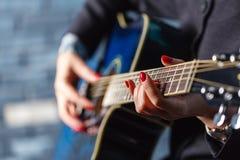 Mão fêmea do close-up que joga na guitarra acústica Imagens de Stock
