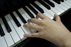 mão fêmea do close-up que joga o piano de cauda foto de stock