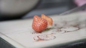 Mão fêmea do cozinheiro chefe que corta as morangos frescas cortadas com uma faca filme