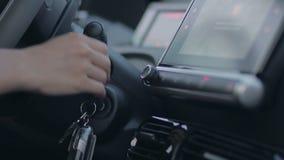 Mão fêmea do motorista que põe a chave de ignição ao buraco da fechadura video estoque