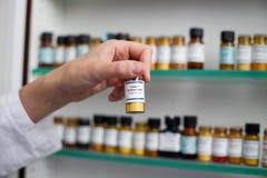 Mão fêmea dos farmacêuticos que guardara a garrafa imagens de stock