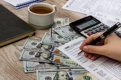 A mão fêmea enche os formulários de imposto 1040 em uma tabela de madeira fotografia de stock royalty free