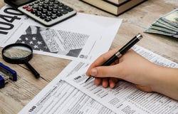 A mão fêmea enche os formulários de imposto 1040 em uma tabela de madeira fotografia de stock