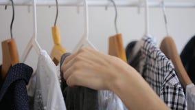 A mão fêmea escolhe a roupa em um gancho vídeos de arquivo