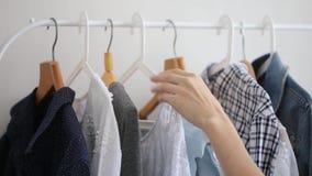 A mão fêmea escolhe a roupa em um gancho filme