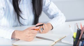 A mão fêmea escreve com uma pena em um caderno do diário fotografia de stock royalty free