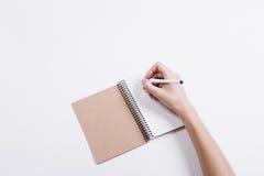 A mão fêmea escreve uma pena em um caderno em uma tabela branca Fotografia de Stock
