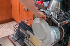 A mão fêmea está dando pratos sujos na máquina de lavar louça foto de stock