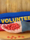 A mão fêmea está guardando muitos corações pequenos em um fundo de madeira Uniforme voluntário no fundo Foto de Stock Royalty Free