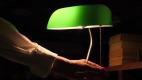 Mão fêmea girada fora do candeeiro de mesa verde na biblioteca 4K filme