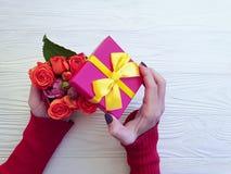 A mão fêmea guarda a curva romântica da celebração da flor do cumprimento da surpresa da caixa de presente, flor cor-de-rosa no f foto de stock