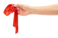A mão fêmea guarda a fita vermelha do papel de embrulho Isolado no fundo branco imagens de stock royalty free