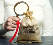 A mão fêmea guarda a lupa sobre o saco e acima a seta do dinheiro Análise de conceito dos lucros e do orçamento na empresa succes fotografia de stock royalty free