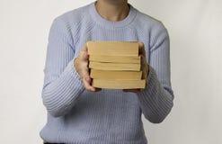 A mão fêmea guarda uma pilha de livros fotos de stock