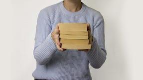 A mão fêmea guarda uma pilha de livros Fotos de Stock Royalty Free