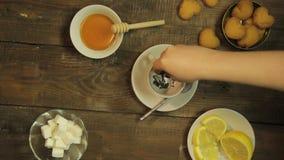 A mão fêmea joga uma pitada do chá verde em um copo vídeos de arquivo