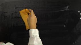 A mão fêmea limpa a placa com as fórmulas video estoque