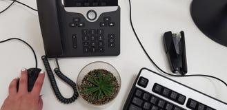 Mão fêmea no rato preto do computador perto do teclado do telefone do escritório imagens de stock
