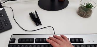 Mão fêmea no teclado de computador preto fotografia de stock royalty free