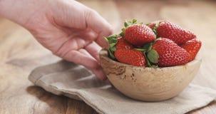 A mão fêmea nova põe a bacia de morangos sobre a tabela Imagens de Stock