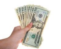 Mão fêmea nova que mantém 20 notas de dólar ventiladas para fora Fotos de Stock