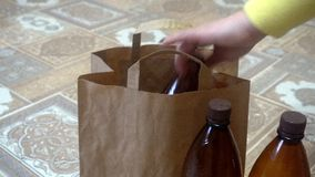 A mão fêmea põe as garrafas plásticas vazias no pacote vídeos de arquivo