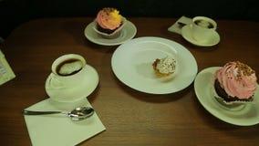 A mão fêmea põe bolos em uma placa branca ao café filme